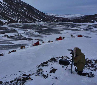 Graduate student Jayme Dittmar films a sled dog team in Alaska for the NPS video.